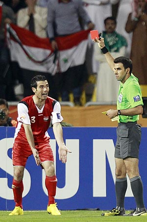 Syria's Nadim Sabag (left) gestures toward referee Mohsen Torky of Iran as he is issued a red card during their Asian Cup Group B match against Japan on Thursday