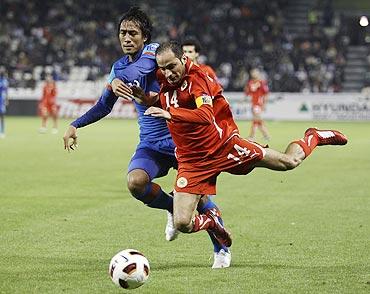 India's Gouramangi Singh (left) and Bahrain's Salman Isa vie for possession