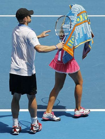 Victoria Azarenka covers her head with a towel as Andy Roddick watches
