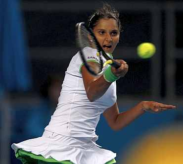 Sania Mirza returns to Justine Henin during her match at the Australian Open
