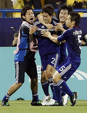 Japan's Masahiko Inoha (centre) celebrates with teammates after scoring the winning goal against Qatar on Friday