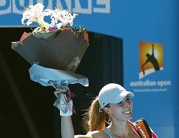 Alize Cornet smiles after receiving a bouquet for her 21st birthday on Saturday