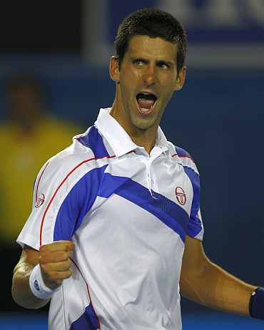 Novak Djokovic celebrates after winning a match against Roger Federer