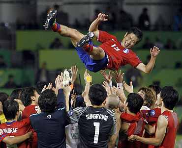 South Korea's players throw Lee Young-pyo in the air after winning their 2011 Asian Cup third place playoff match against Uzbekistan