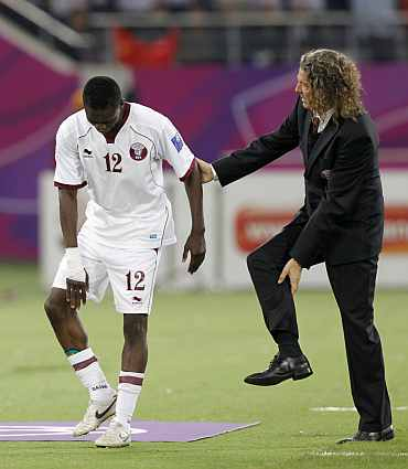 Qatar's coach Bruno Metsu speaks to his player Yusef Ahmed during a match