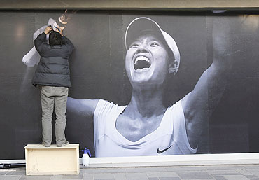 A worker puts up a poster of Chinese tennis player Li Na at a shopping district in Beijing