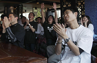 Fans cheer as they watch the Australian Open women's final in a bar in central Beijing
