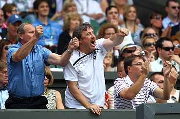 Petra Kvitova's support team including her father Jiri Kvitova cheer during her Ladies' final round match against Maria Sharapova