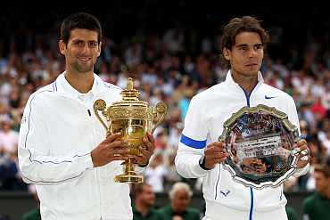 Winner Novak Djokovic (L) and runner-up Rafael Nadal with their trophies after their Wimbledon final on Sunday