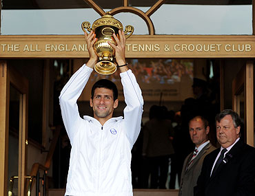 Novak Djokovic holds the championship trophy outside the members entrance at the at the All England Lawn Tennis and Croquet Club on Sunday