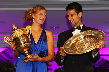 Novak Djokovic and Petra Kvitova swap their respective trophies at the Wimbledon Championships 2011 Winners Ball on Sunday