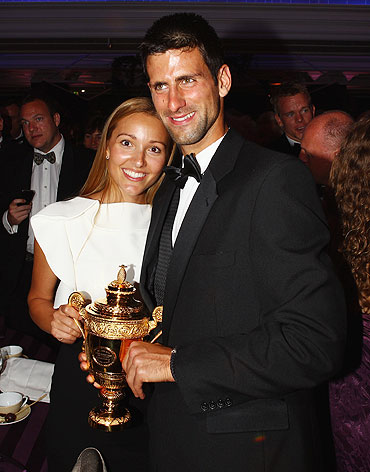 Novak Djokovic and girlfriend Jelena Ristic pose with the replica of the mens trophy at the Winners Ball on Sunday