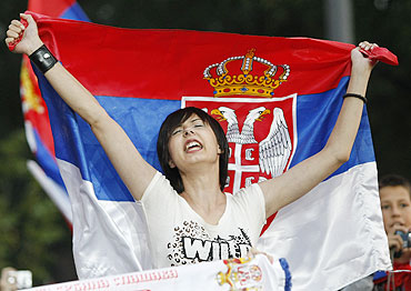 A girl waves the Serbian flag to celebrate Novak Djokovic's arrival in Belgrade on Monday