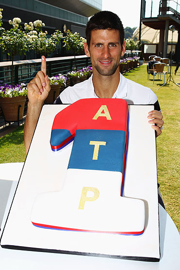 Novak Djokovic poses with a cake decorated in the colours of the Serbian flag as he celebrates becoming the new World number one on Monday