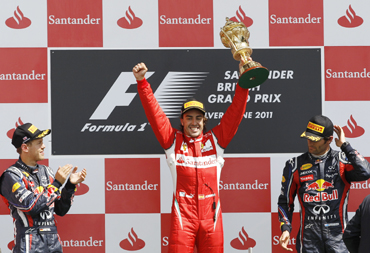 Ferrari Formula One driver Fernando Alonso (C) of Spain celebrates winning the British F1 Grand Prix as third placed Red Bull driver Mark Webber and second placed Red Bull driver Sebastian Vettel