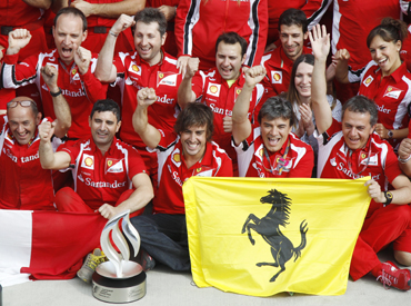 Ferrari's Formula One team poses in their pit garage after driver Fernando Alonso of Spain (C) won the British F1 Grand Prix at Silverstone