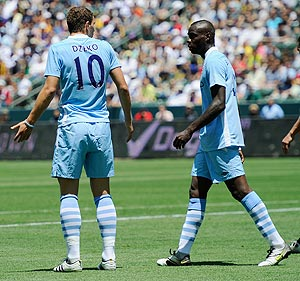 Manchester City's Edin Dzeko has words with teammate Mario Balotelli after the latter blasted the ball into the net he inexplicably tried to score with a spinning backheel which went wide of the target against the Los Angeles Galaxy on Sunday