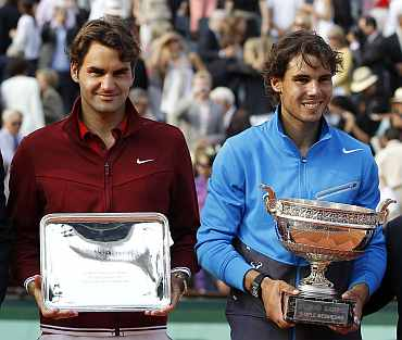 Rafa Nadal and Roger Federer pose with their trophies after their men's final at the French Open