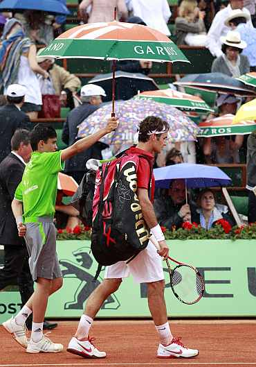 Roger Federer leaves the court as rain stops the play during his men's final match against Rafa Nadal at the French Open