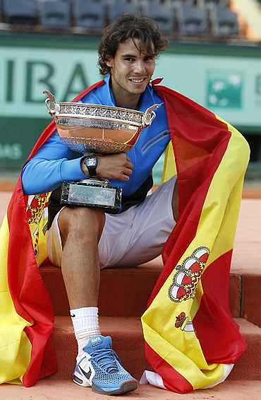 Rafa Nadal poses with the trophy and the Spanish flag during the ceremony after defeating Federer during their men's final at the French Open