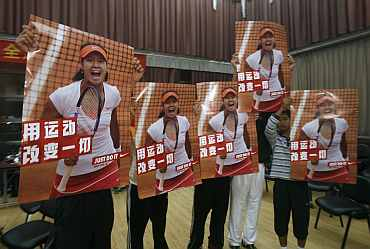 Local tennis students hold posters featuring Chinese tennis player Li Na in her hometown of Wuhan