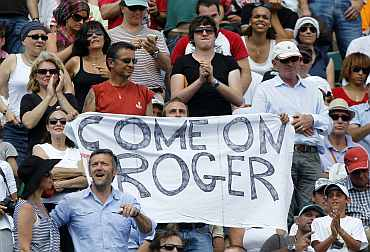 A supporter of Roger Federer holds a banner during the men's final at the French Open