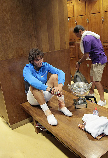 Rafael Nadal rests with his French Open trophy in the players dressing room