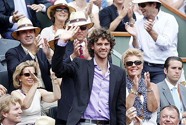 Former tennis player Gustavo Kuerten of Brazil waves as he arrives to watch the men's final match between Rafael Nadal and Roger Federer