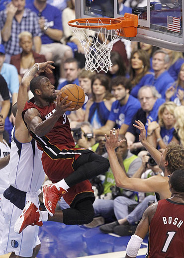 Miami Heat's Dwyane Wade (centre) goes up for a basket against the Dallas Mavericks