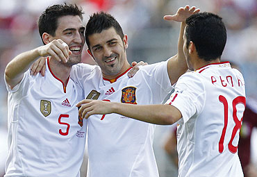 Spain's David Villa (centre) celebrates with teammates Andoni Iraola (left) and Pedro Rodriguez after scoring against Venezuela