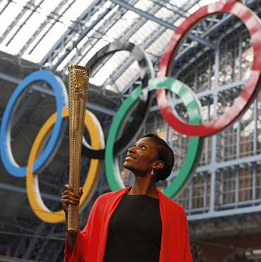 Olympic gold medalist Denise Lewis poses with a prototype of the London 2012 Olympic Torch at St Pancras station in London