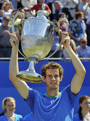 Andy Murray of Britain holds up The Queen's Cup trophy
