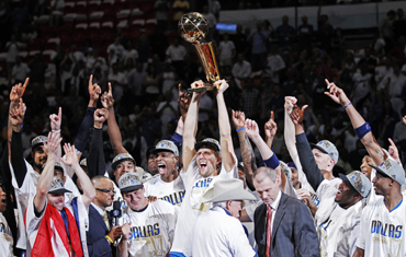 Dallas Mavericks' Dirk Nowitzki lifts the Larry O'Brien Championship Trophy with his teammates after they beat the Miami Heat in Game 6 to win the NBA Finals basketball series in Miami