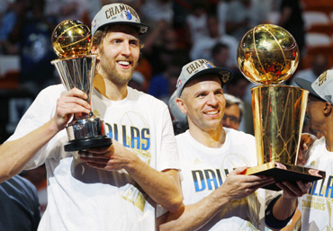 Mavericks' Nowitzki holds the Bill Russell NBA Finals MVP trophy as Kidd holds the Larry O'Brien Championship Trophy