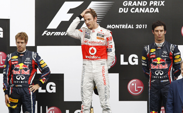 McLaren driver Jenson Button of Britain (C), Red Bull driver Sebastian Vettel (L) and third place Mark Webber stand on the podium