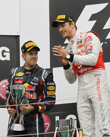 McLaren Formula One driver Jenson Button (R) of Britain applauds as second place finisher Red Bull Formula One driver Sebastian Vettel holds his tropohy after the Canadian F1 Grand Prix