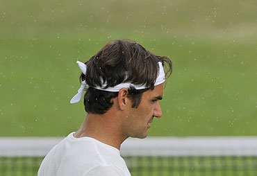 Roger Federer trains in the rain on a practice court on Sunday
