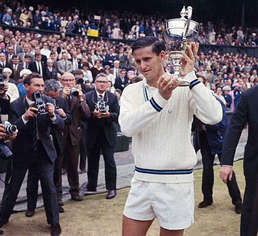 Australian tennis player Roy Emerson raises the men's singles trophy after beating fellow-Australian Fred Stolle in the 1965 Wimbledon final