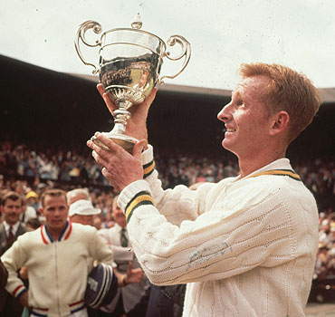 Rod Laver of Australia lifts the men's singles trophy after beating Chuck McKinley of the United States in 1961