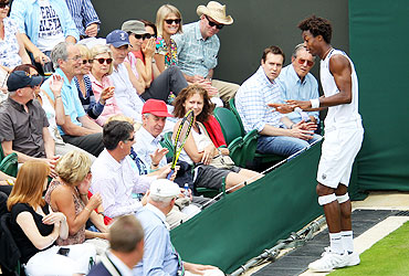 Gael Monfils retrieves his racket from the crowd during his first round match against Matthias Bachinger