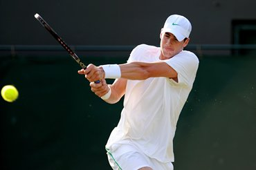 John Isner returns a shot