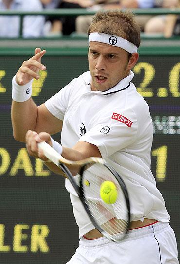 Gilles Muller hits a return to Rafael Nadal
