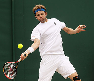 Mardy Fish returns a shot against Robin Haase