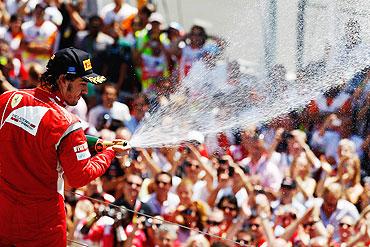 Ferrari's Fernando Alonso celebrates on the podium after finishing second during the European Formula One Grand Prix