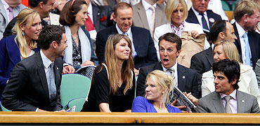 England cricketers James Anderson (left), Graeme Swann (2nd from right) and Alastair Cook (right) have a laugh before the match between Serena Williams and Aravane Rezai