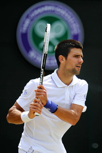 Novak Djokovic of Serbia returns a shot during his quarterfinal round match against Bernard Tomic of Australia on Day Nine of the Wimbledon Championships