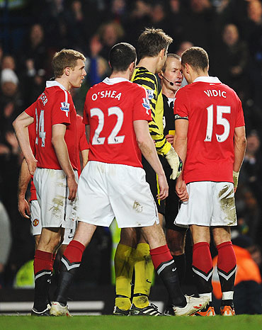 Nemanja Vidic of Manchester United goes head to head with referee Martin Atkinson after being shown the red card
