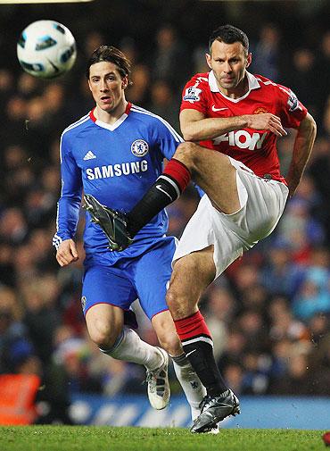 Ryan Giggs of passes as Fernando Torres looks on