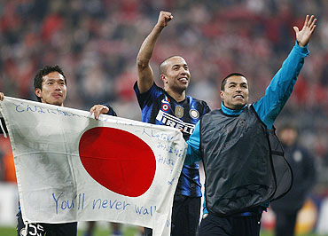 Inter Milan's Yuto Nagatomo (left) holds up a Japanese flag and celebrates with teammate Houssine Kharja (centre) after their win over Bayern Munich on Wednesday