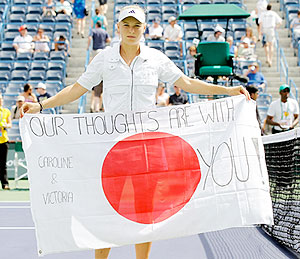 Caroline Wozniacki of Denmark holds a flag dedicated to the people of Japan after her match against Victoria Azarenka of Russia on Thursday